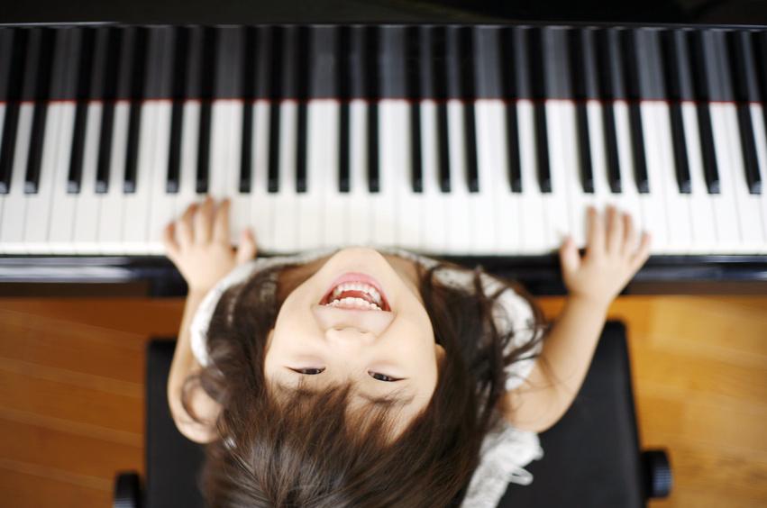 ピアノを弾く女の子 やっぱりアコースティックピアノがいいね。アコースティックピアノは、お子様の感性をより豊かに育みます。